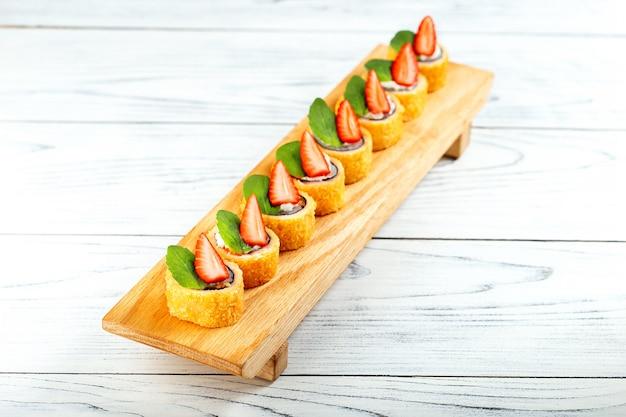 Rotolo di sushi dolce con la fragola sul piatto di legno. nuova tendenza nella cuisiune giapponese.