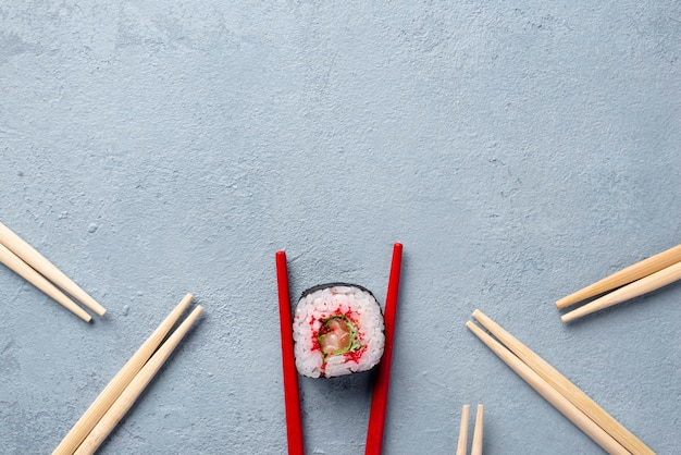 Rotolo di sushi e bacchette di maki di vista superiore con lo spazio della copia