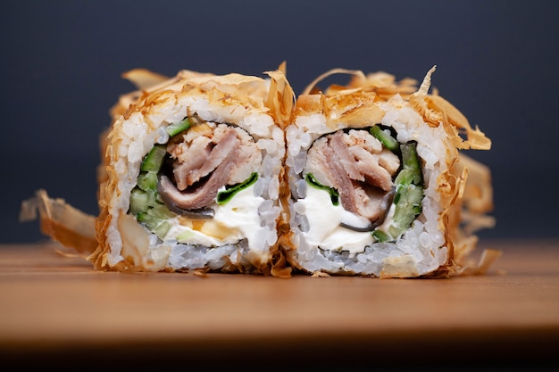 Rotolo di sushi giapponese con i salmoni ed il cetriolo su oscurità