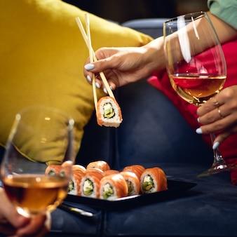 Rotolo di sushi philadelphia con salmone, anguilla affumicata, avocado, crema di formaggio sul divano. coppia con bicchieri di vino. cibo giapponese