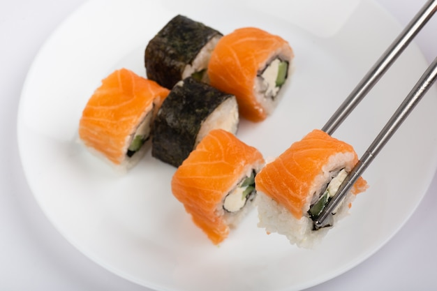 Rotolo di sushi sulle bacchette con rotolo di sushi sul piatto bianco su sfondo bianco
