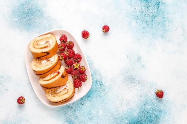 Rotolo di torta ai lamponi con frutti di bosco freschi.