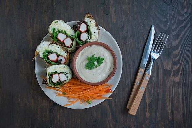Rotolo di zucchine con bastoncini di granchio, uova e spinaci.