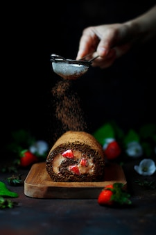 Rotolo dolce della fragola del cioccolato con le fragole levitanti e le mani della donna, fotografia scura dell'alimento