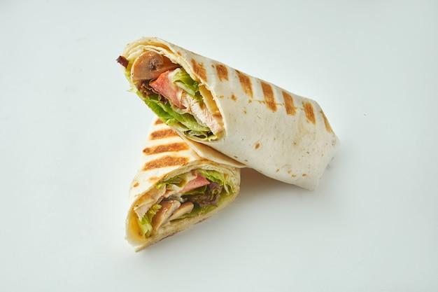 Rotolo fresco con pollo, pomodori, formaggio e lattuga nel pane pita su un tavolo bianco. pollo al forno shawarma