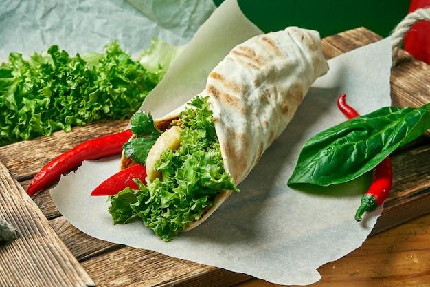 Rotolo vegetariano di shawarma in pita con lattuga, verdure e banana. cibo gustoso, sano e verde. cibo da strada vegano