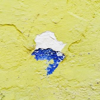 Rotto muro giallo con blu