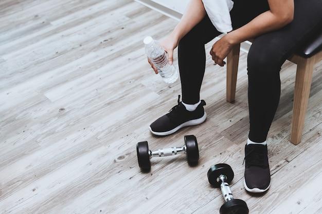Rottura della ragazza di forma fisica per acqua potabile che si siede con l'allenamento con i pesi delle teste di legno con copyspace