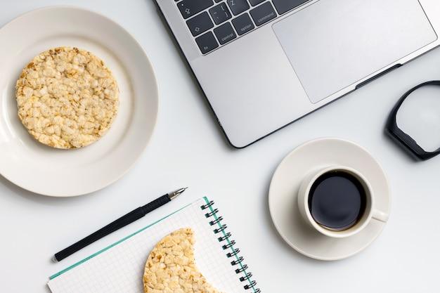 Round di riso croccante con caffè vicino al laptop e al notebook.