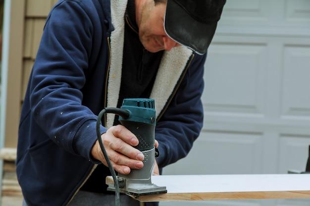 Router a base fissa elettrica portatile con guanti da lavoro su legno