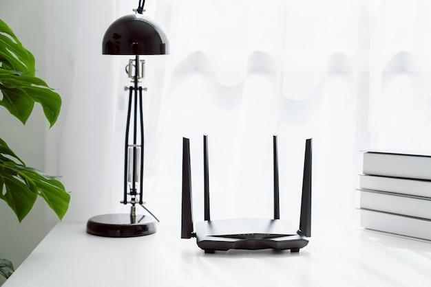 Router di banda larga e di wifi sulla tavola bianca