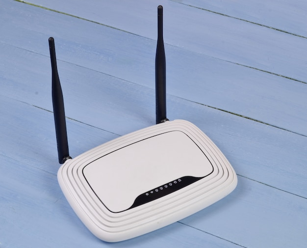 Router wi-fi con antenne su un tavolo di legno blu