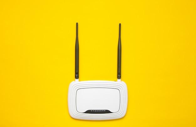 Router wi-fi su uno sfondo giallo. tendenza del minimalismo. sempre online. vista dall'alto.