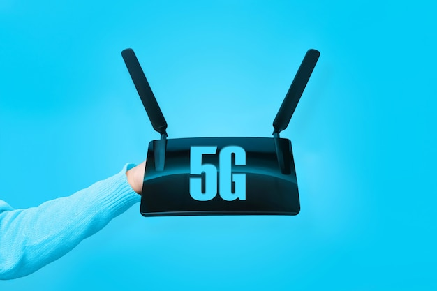 Router wifi nero a portata di mano e scritta 5g