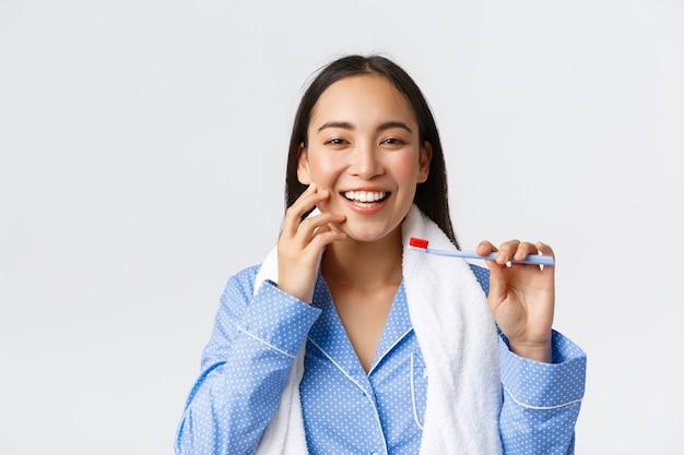 Routine quotidiana, mattina e concetto di igiene. primo piano della splendida ragazza asiatica con un sorriso bianco perfetto e pelle pulita che tiene asciugamano e spazzolino da denti, lavarsi i denti in pigiama blu, muro bianco