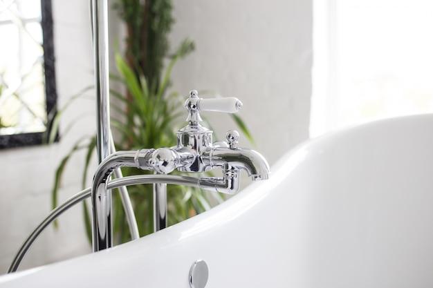 Rubinetto con doccia in primo piano bagno. luminosa camera bianca con verdure.