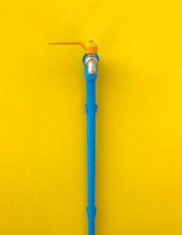 Rubinetto con la tubatura dell'acqua blu sulla parete gialla.