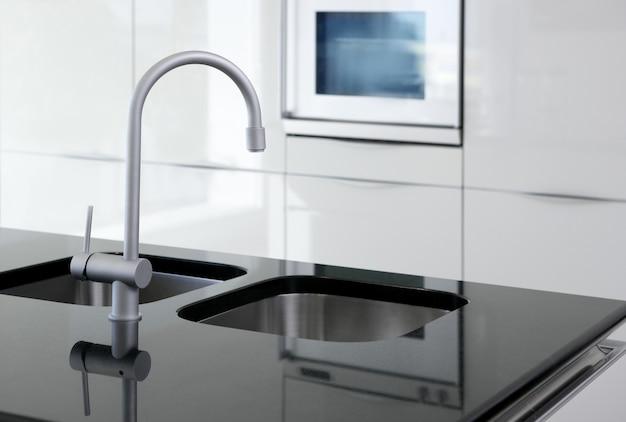 Rubinetto della cucina e moderno forno bianco e nero