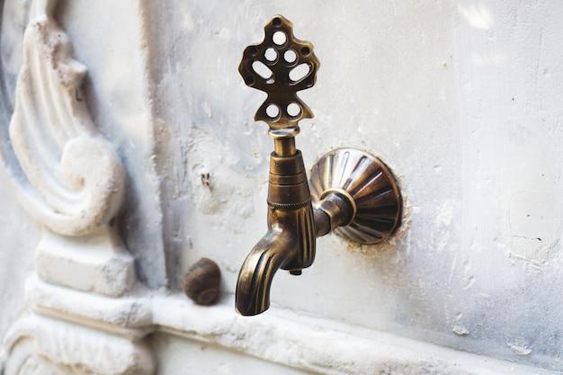 Rubinetto di acqua d'annata di stile turco dell'ottomano alla fontana di abluzione nell'iarda.