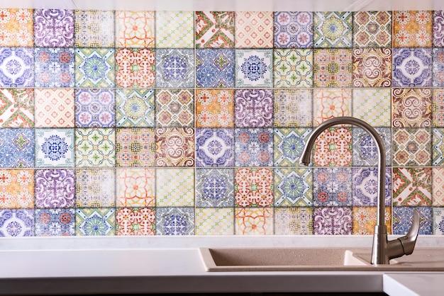 Rubinetto in acciaio inossidabile lucido con rubinetto cromato, lavello in pietra e piano di lavoro contro un muro di vecchie piastrelle colorate. interno cucina