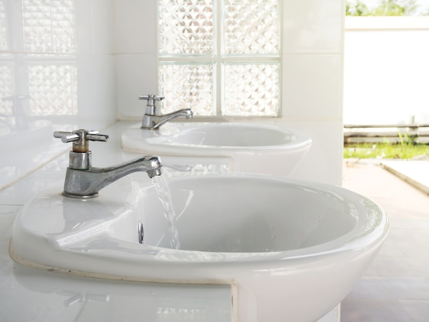 Rubinetto metallico con accendere il flusso d'acqua nella toilette pubblica. concetto di pulizia