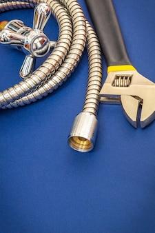 Rubinetto per materiali idraulici, utensile e tubo flessibile su sfondo blu vengono utilizzati per la sostituzione sotto la doccia