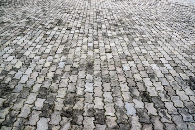 Ruggine ed erosione del tono grigio del pavimento di mattoni antichi