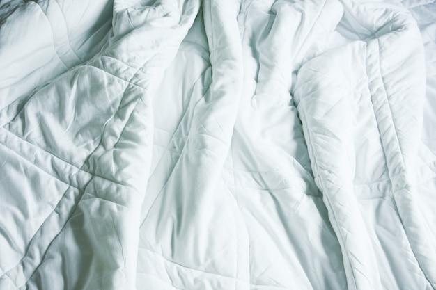 Rugosa coperta disordinata in camera da letto dopo essersi svegliati la mattina, dal dormire in una lunga notte, dettagli di piumone e coperta, un letto sfatto nella camera d'albergo con una coperta bianca.