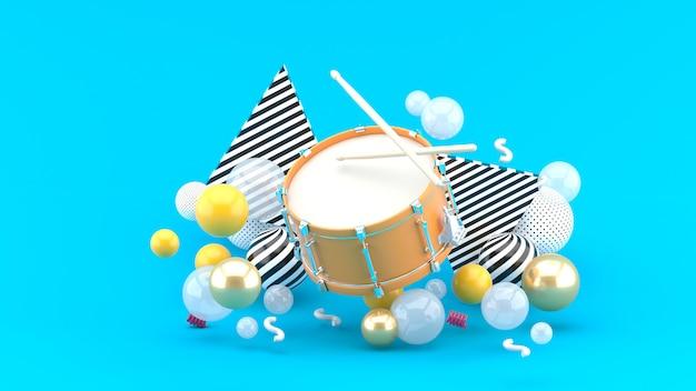 Rullante arancione tra le palline colorate sul blu. rendering 3d.