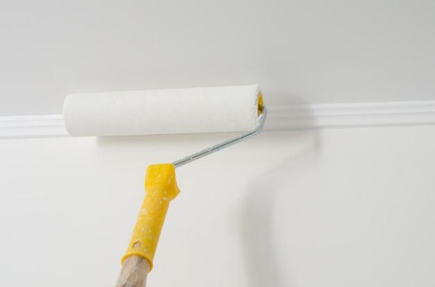 Rullo di vernice con manico giallo. processo di verniciatura a soffitto e parete. bianca . copyspace