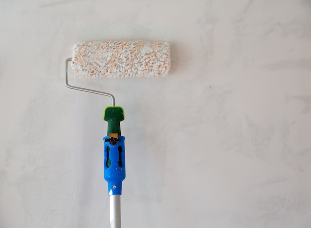 Rullo di vernice per dipingere il muro dopo l'intonacatura