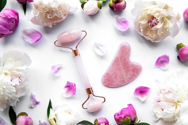 Rullo facciale in giada per massoterapia facciale di bellezza e peonie rosa. lay piatto sulla superficie bianca