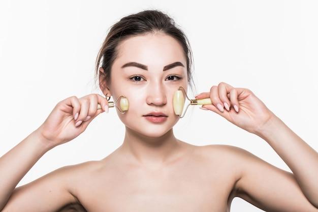 Rullo facciale in pietra di giada rosa per la terapia del massaggio facciale. ritratto del rullo asiatico di invecchiamento della giada di uso della donna isolato sulla parete bianca.