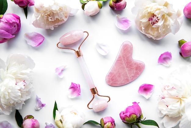 Rullo viso in giada per la terapia del massaggio facciale di bellezza e peonie rosa. piatto giaceva su sfondo bianco