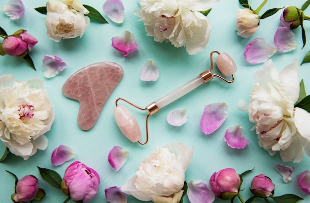 Rullo viso in giada per la terapia del massaggio facciale di bellezza e peonie rosa. piatto giaceva su sfondo blu pastello