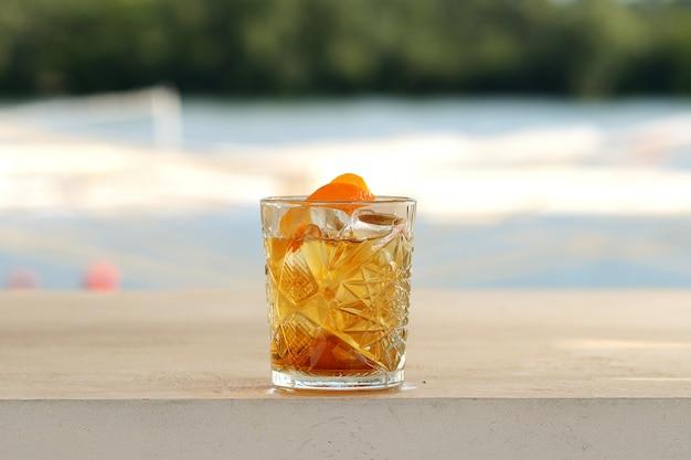 Rum in un bicchiere con ghiaccio e buccia d'arancia