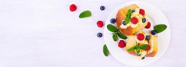 Rum panini salati decorati con panna montata e frutti di bosco freschi