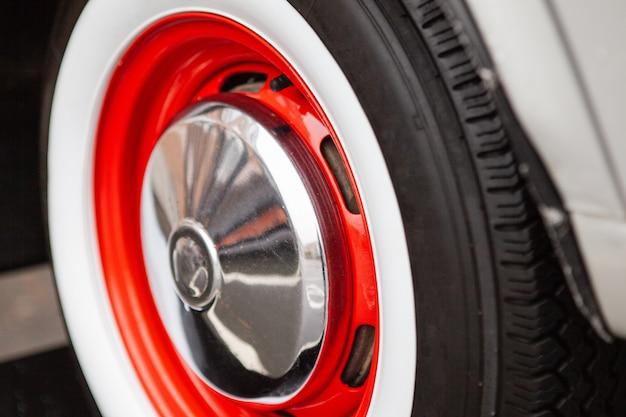 Ruota auto d'epoca, dipinta di rosso, il concetto della storia dello sviluppo delle auto.