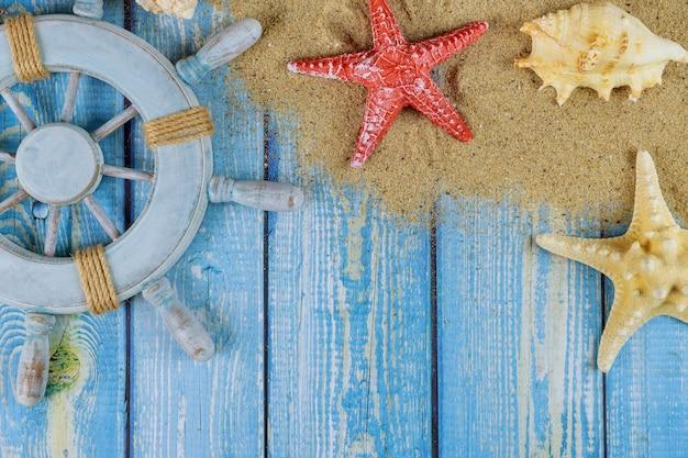 Ruota del capitano del marinaio con conchiglie, stelle marine, sabbia, tavole di legno blu