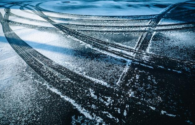 Ruota di automobile sull'estratto del fondo di inverno di stagione della neve