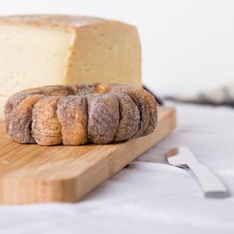 Ruota di fichi secchi con un fico secco tagliato a fette accanto a pezzi di formaggio pecorino in cima a tavola di legno su una tovaglia bianca con un coltello di metallo