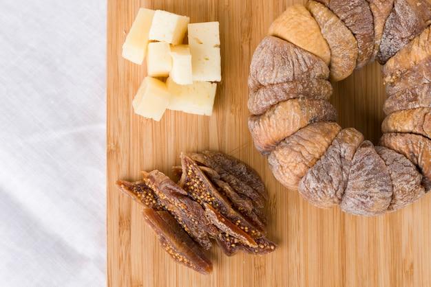 Ruota di fichi secchi con un fico secco tagliato a fette accanto a pezzi di formaggio pecorino