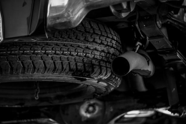 Ruota di scorta sotto la macchina vicino al tubo di scarico. ruota di scorta. prodotto in gomma. controllo dell'automobile prima del concetto di viaggio. ruota di scorta per camion. concetto di cambiamento nel servizio di assistenza pneumatici. industria automobilistica.