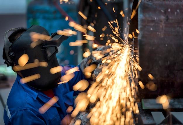 Ruota elettrica che macina sul tubo d'acciaio in fabbrica
