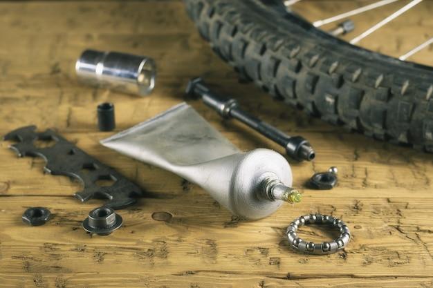 Ruota in mountain bike e ingrassa sul tavolo di legno.