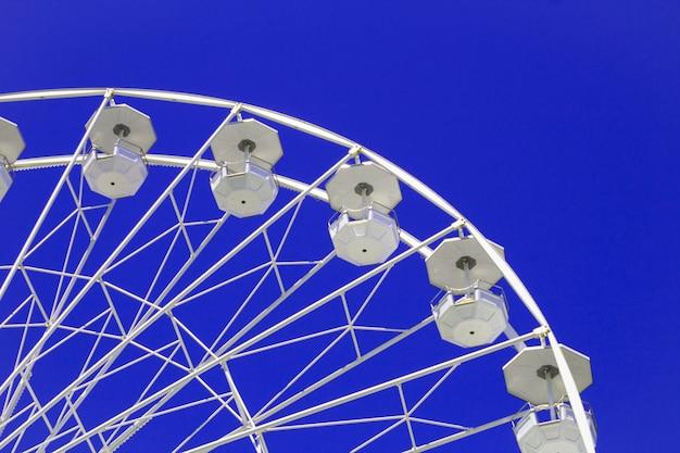 Ruota panoramica bianca sul cielo blu luminoso. copia spazio. avvicinamento.