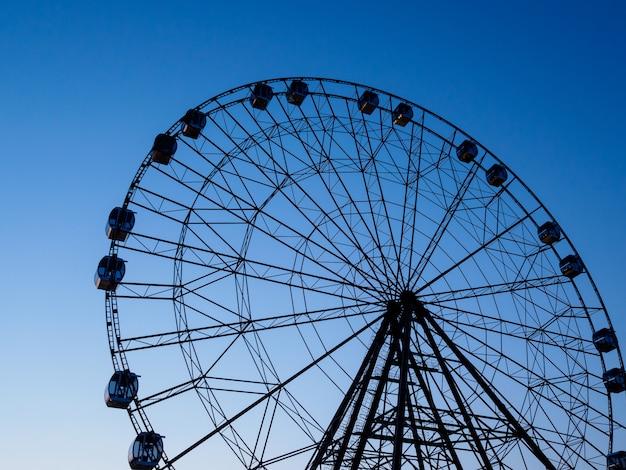 Ruota panoramica in un parco di divertimenti sulla a del cielo al tramonto. luce del regime.