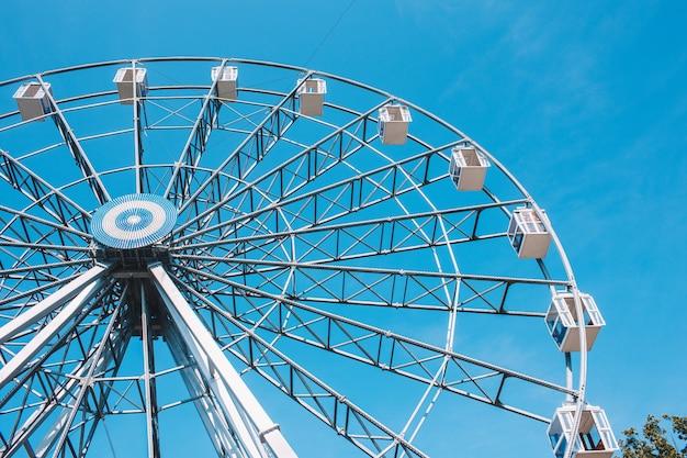 Ruota panoramica in un parco su uno sfondo blu chiaro.