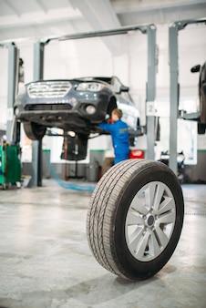 Ruota sul pavimento nel servizio di pneumatici, riparatore lavora con l'auto sull'ascensore