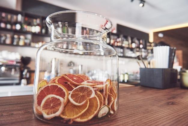 Ruote secche di arancia candita, lime e limone in un grande contenitore di vetro con contenuto disposto anche su macelleria attorno a barattolo con zucchero grezzo e coperchio in metallo